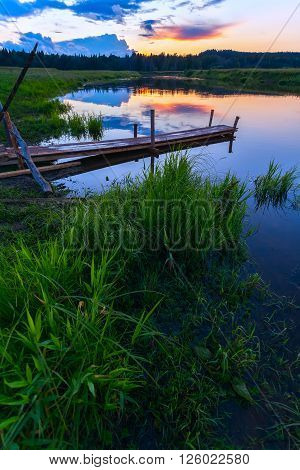 Lake and wooden bridge at sunset landscape