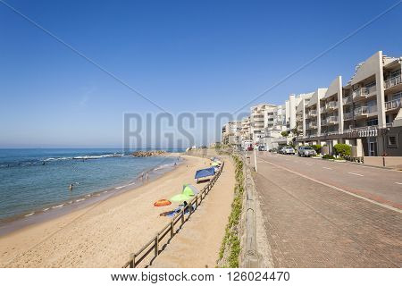 Beach ocean tidal pool swimmers with holiday apartments coastline landscape.