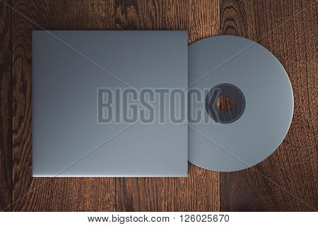 Topview of blank grey compact disk with cover on wooden table. Mock up 3D Rendering