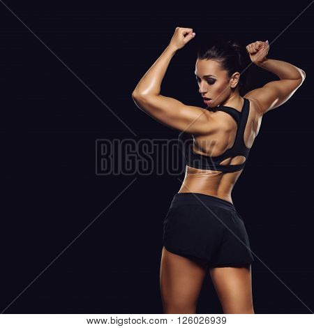 Sporty fit beautiful woman with muscle relief. Over black backgound. Copy space. Square composition.