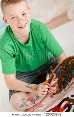 Slanted View Of Boy With Paint On Legs And Hands