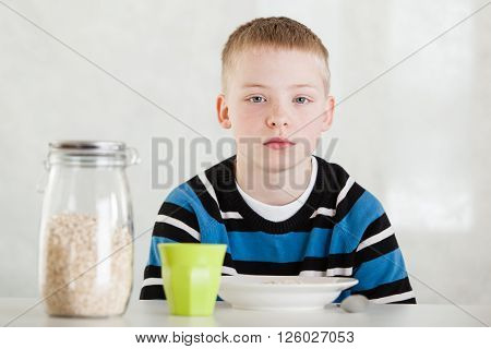Child Next To Jar Of Oats, Cup And Bowl On Table