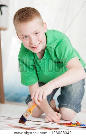Boy Kneeling On Painting While Holding Brush
