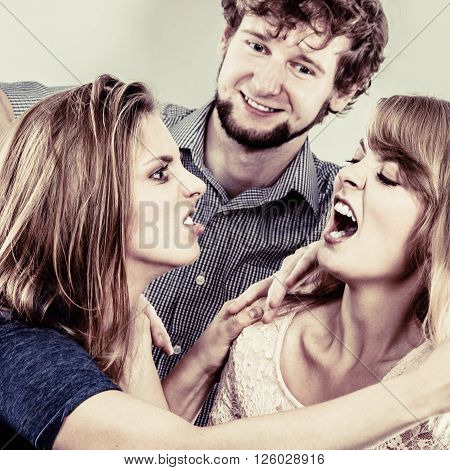 Aggressive mad women fighting over man. Young jealous girls wooing guy. Violence.