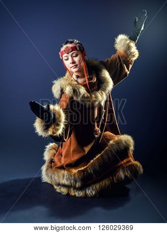 Beautiful young girl dancing a ritual dance in traditional costume of the small Northern peoples.