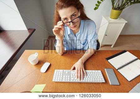 Confident Attractive Female Entrepreneur Looking At The Camera While Taking Off Her Glasses. Portrai