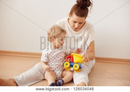 Happy Family Enjoying Free Time At Home In Sweet Morning, Sitting On The Floor Against White Backgro
