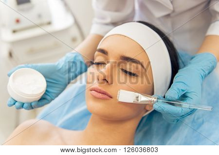 Beautiful young woman is getting face skin treatment. Doctor in medical gloves is holding a bottle of cream and a brush