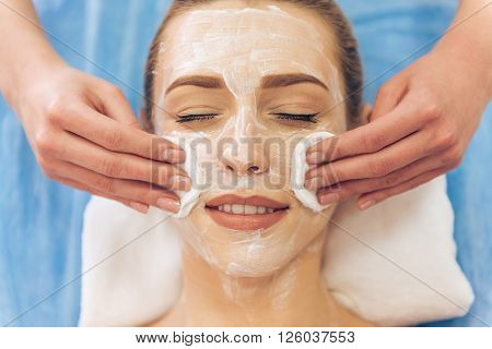 Top view of beautiful young woman getting face skin treatment. Cosmetician is undertaking the procedure using sponges