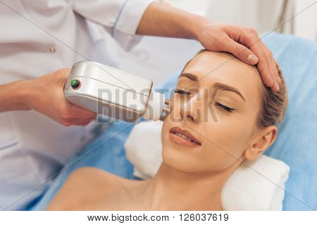Beautiful woman is getting face skin treatment. Doctor is undertaking the procedure using a modern equipment