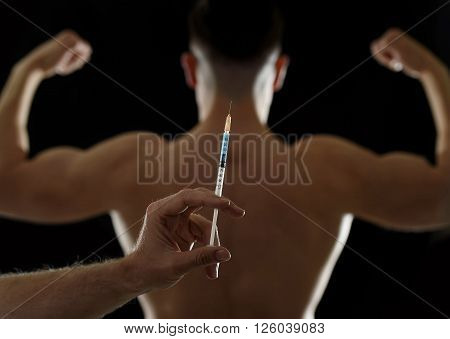 strong back of young body building sportsman using steroids for increasing sport athletic performance and hand holding syringe in sport cheat doping and illegal use of hormones concept