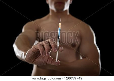 young body building sportsman using steroids for increasing sport and athletic performance holding close up syringe isolated on back background in sport cheat doping and illegal use of hormones