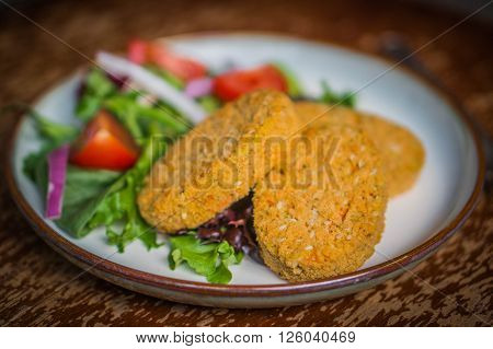 Image of Chicken Nuggets With Salad on rustic background