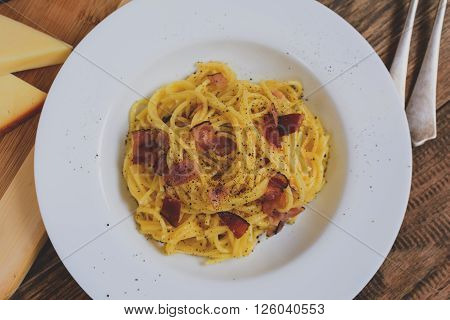 Traditional italian pasta spaghetti alla carbonara with becon cheese and agg yolk on white plate