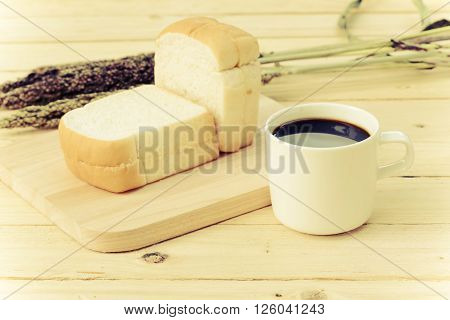 Coffee cup and bread on wooden floor in vintage