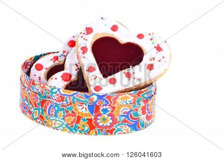 Some butter shortbread cookies heart stuffed with shaped jelly on the nice colorful bow isolated on the white. Romantic treat concept.