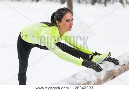 Fitness model athlete warm up stretching her hamstrings, leg and back. Young woman exercising outdoors winter in park