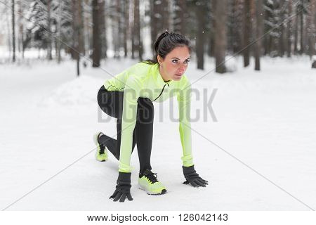 Sportive athlete woman sprinter ready to run waiting for the start running position fitness, sport, training.
