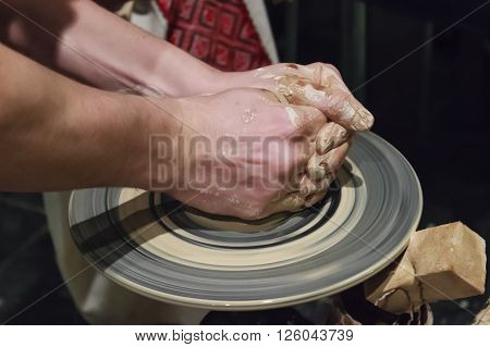 Hands of a potter, who makes dishes out of clay
