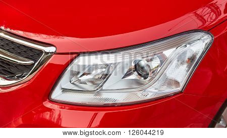 Headlight on modern red car on outdoor
