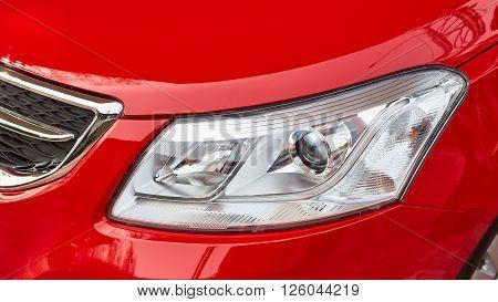 Headlight on modern red car on outdoor