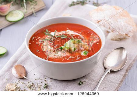 fresh tomato soup in a grey bowl. Traditional spanish soup gazpacho with herbs, little croutons, pepper and fresh cucumbers.