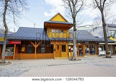 ZAKOPANE POLAND - MARCH 09 2016: Residential and commercial building made of wood in approx. 1895 located at Krupowki the main pedestrian street in the city