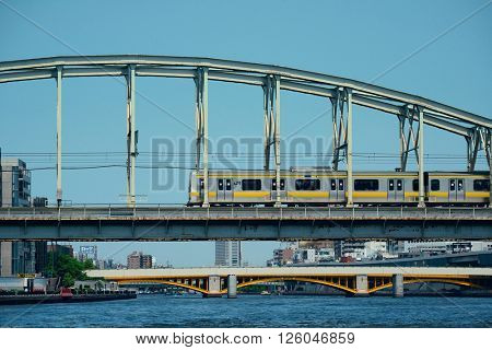 TOKYO, JAPAN - MAY 15: Train on bridge on May 15, 2013 in Tokyo. Tokyo is the capital of Japan and the most populous metropolitan area in the world
