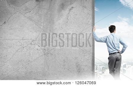 Businessman standing with back and leaning on cement blank wall
