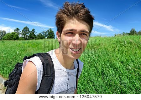 Young Man with Knapsack walk in the Summer Field