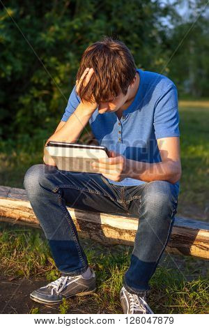 Sad Young Man with Tablet Computer on the Wooden Bench