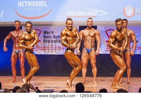 MAASTRICHT THE NETHERLANDS - OCTOBER 25 2015: Male bodybuilders Ali Rezah from Iran with other competitors flex their muscles and show their best physique in a chest pose on stage at the World Grandprix Bodybuilding and Fitness of the WBBF-WFF