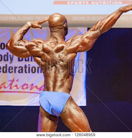 MAASTRICHT THE NETHERLANDS - OCTOBER 25 2015: Male bodybuilder Elias Bogane flexes his muscles and shows his best physique in a back pose on stage at the World Grandprix Bodybuilding and Fitness of the WBBF-WFF