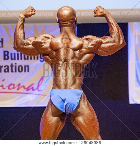MAASTRICHT THE NETHERLANDS - OCTOBER 25 2015: Male bodybuilder Elias Bogane flexes his muscles and shows his best physique in a back double biceps pose on stage at the World Grandprix Bodybuilding and Fitness of the WBBF-WFF