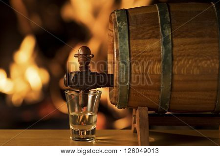 Cachaça Barrel, Brazilian drink / Cachaça being poured into a small glass from a barrel with a fireplace on the background