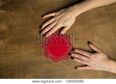 Hand-Knitted linen table napkin handmade on wood background with woman hands