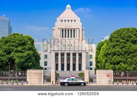 TOKYO, JAPAN - JULY 31 2015: Officers sit in a police cruiser below The National Diet Building of Japan.