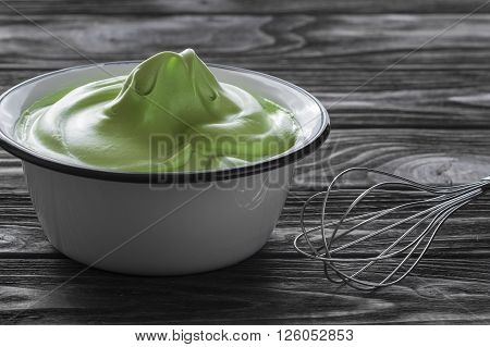 green bright cream in white plate on wooden table