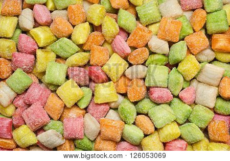 Colorful fruit candy without wrappers, in the form of pads. Textured background of sweets.