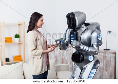 Help me. Cheerful positive charming girl using tablet  and smiling  while giving it to the robot