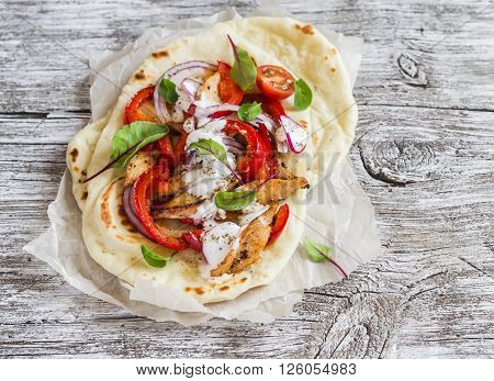 Naan bread and chicken vegetables stir fry in light wood rustic background. Delicious food