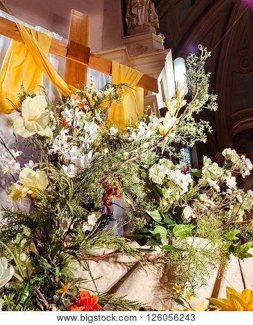 Colorful flowers over Christ cross in catholic church mass closeup