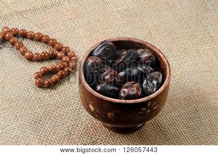 Ramadan fresh dates in a wooden bowl with rosary.** Note: Visible grain at 100%, best at smaller sizes