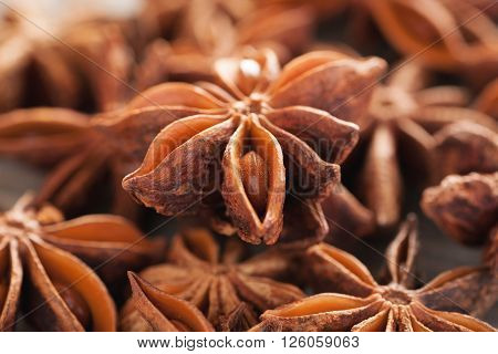 Heap of star anise on a wooden table closeup macro shot selective focus