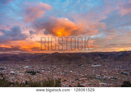 Panoramic view of Cusco town with glowing cloudscape and colorful sky at dusk. Cusco is among the most important travel destination in Peru and the entire South America.