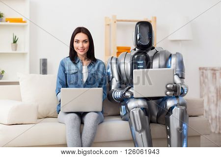 Happy together. Cheerful delighted attractive girl sitting on the couch with robot and smiling while using laptops