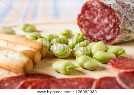 Close up of broad bean and bread sticks with Italian salami over a chopping board