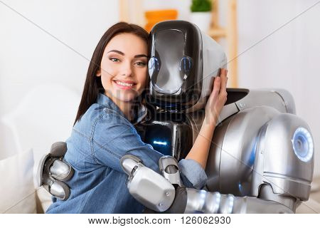 Seize the moment. Cheerful delighted beautiful girl sitting  on the sofa with robot and expressing joy while embracing