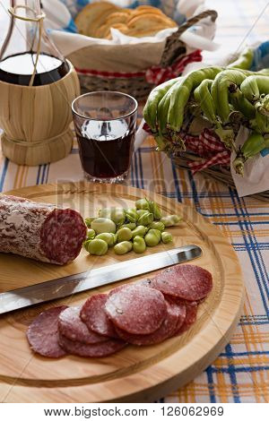Meat chopping board of traditional Italian salami with broad bean and red wine