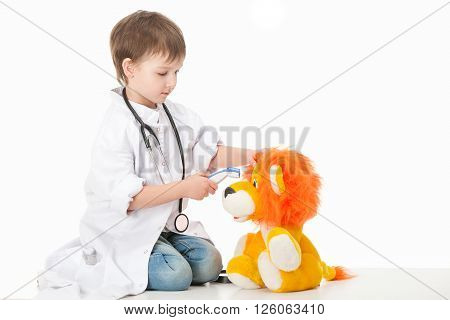 Baby boy in a white robe doctor mereet body temperature of the device at the cub toy . Isolated on white background